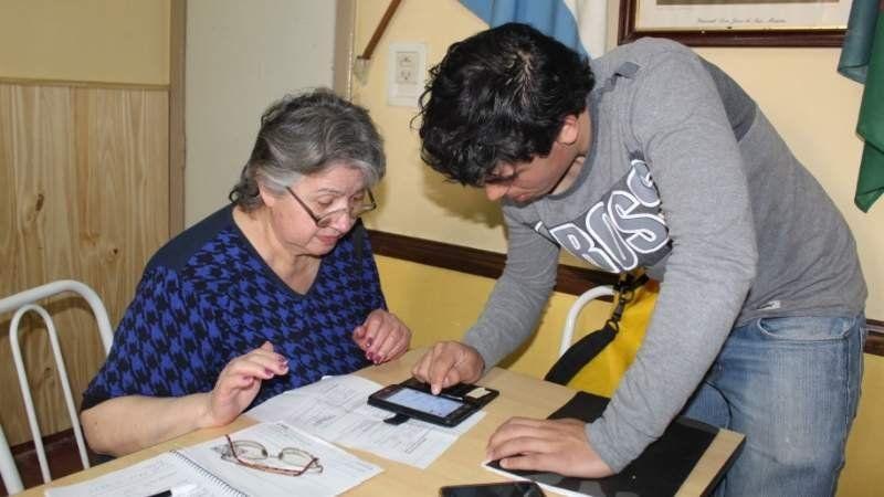 Un joven de San Vicente les enseña a los abuelos a usar el celular en el centro de jubilados