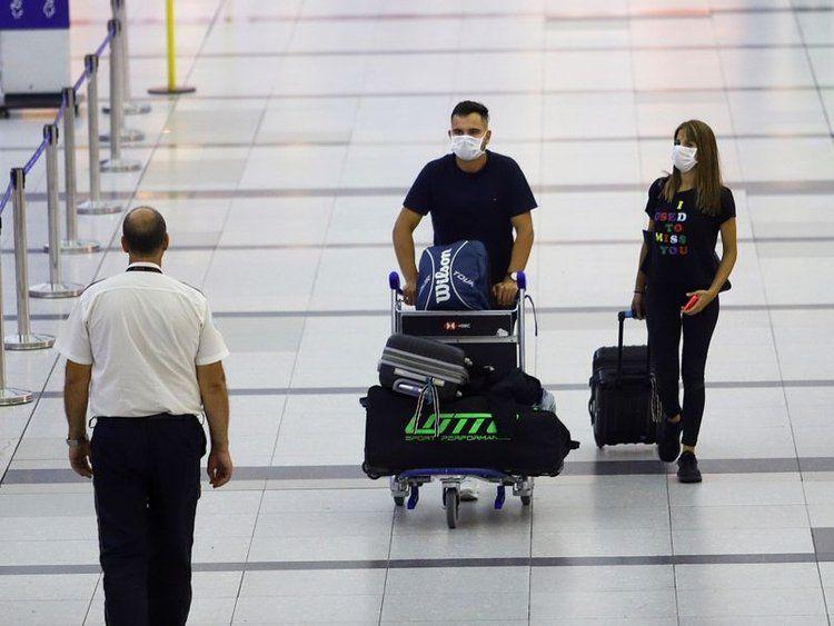 Viajeros caminando con barbijos por el aeropuerto de Ezeiza.