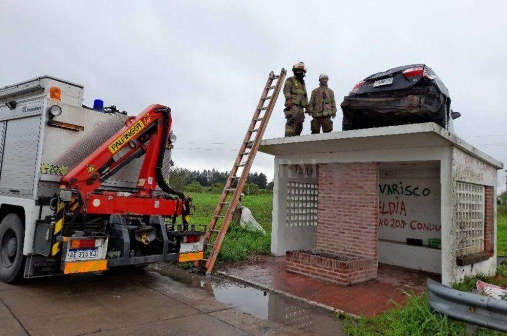 El auto que terminó encima de la parada de colectivos tuvo que ser sacado por los bomberos.